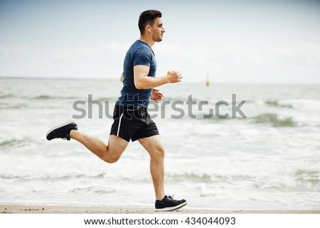 Man running on sunny; beach - stock photo