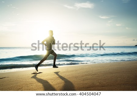 Man running on tropical beach at sunset - stock photo