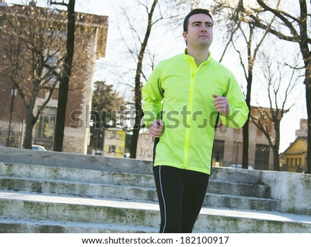man running outside in the city park - stock photo
