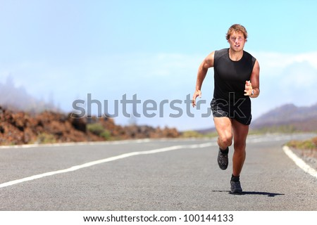 Man running / sprinting on road in mountains. Fit male fitness runner during outdoor workout. Young caucasian man. - stock photo