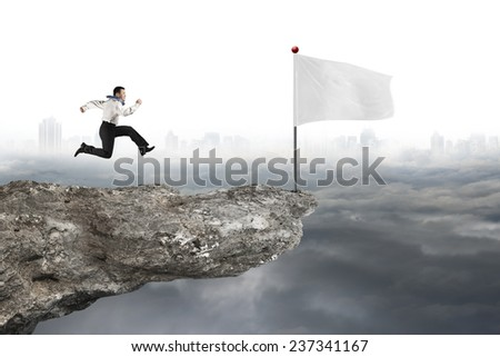 man running to blank white flag on cliff with gray cloudy cityscape background - stock photo