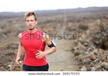 Man running - trail runner cross country training outdoors for marathon or triathlon ironman. Handsome male athlete working out on Hawaii, Big Island, USA. Triathlete listening to music on smart phone - stock photo