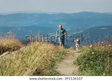 Man runs with his dog on the green meadow in mountain - stock photo