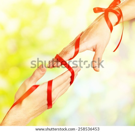 Man's and woman's hands tied with ribbon on sunny nature background - stock photo