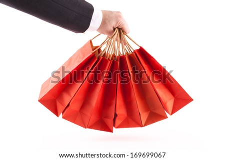 Man's arm holding shopping bags while wearing a suit and white shirt, all on a white background - stock photo