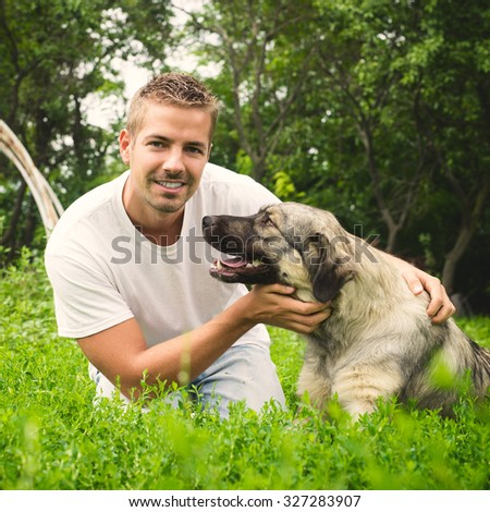 Man's best friend. Man is looking at camera while dog is looking at man.  - stock photo