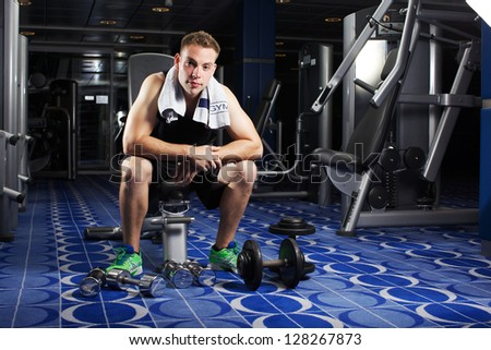 man's body with metal dumbbell on a grey background - stock photo