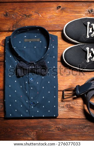 Man's collection of clothes in casual style consisting of a shirt with a bow tie, footwear (sneakers) and belt on a wooden background - stock photo