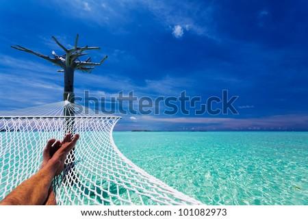 Man's crossed legs in hammock over tropical lagoon - stock photo