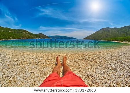 Man's feet relaxing in a Beatiful Bay with Clear blue water - stock photo