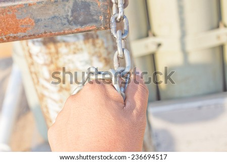man's hand and a metal chain - stock photo