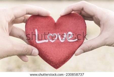 man's hand and woman's hand holding a red heart - stock photo