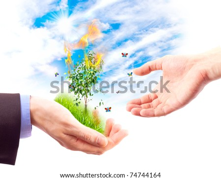 Man's hand gives the other hand, a piece of nature in flames. Concept of saving nature from fire. Collage. - stock photo