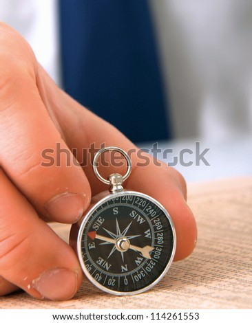 Man's hand holding a compass. - stock photo