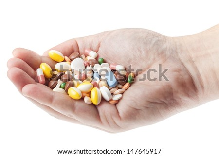 Man's hand holding a handful of medicine pills isolated on white background - stock photo