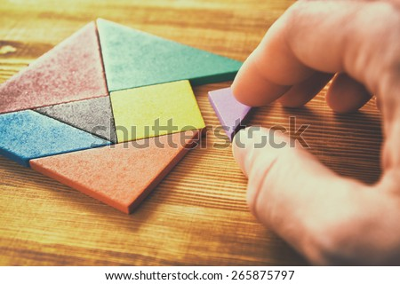 man's hand holding a missing piece in a square tangram puzzle, over wooden table. - stock photo