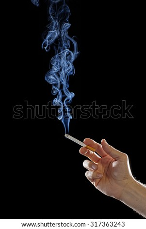 Man's Hand Holding a Smoking Cigarette isolated on Black Background. Close up with White Cigarette Smoke. Copy Space for Text or Image - stock photo