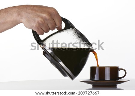 man's hand holding and pouring coffee into a brown cup - stock photo