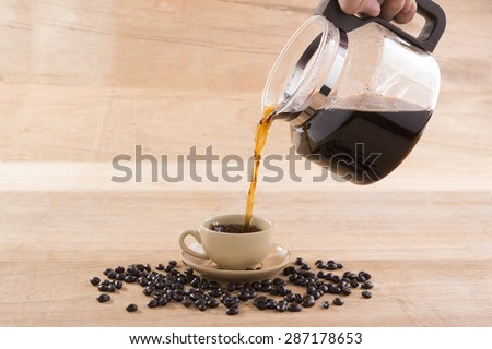 man's hand holding and pouring coffee into cup - stock photo