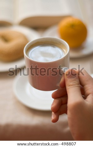 man's hand holding cup of coffee, about to drink - stock photo