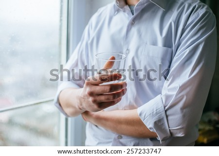 man's hand holding glass with water - stock photo