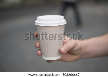 man's hand holding paper cup of coffee. Drink on street on floor background. Good morning concept. Empty space for inscription. No face Unrecognizable person - stock photo