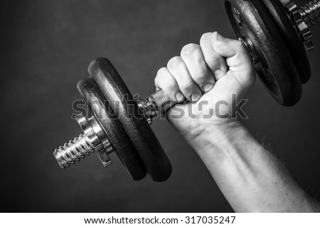 Man`s hand holding weight. Body building in studio, black and white. - stock photo