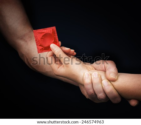 Man's hand holding woman hand with a red condom in a black background - stock photo