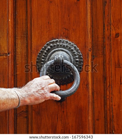 Man's hand holds the cast iron door knocker on the old door in Italy - stock photo
