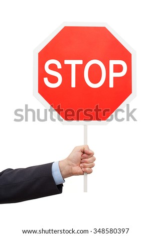 Man's hand in a blue shirt and jacket is holding a red sign STOP. The objects are isolated on white background. - stock photo