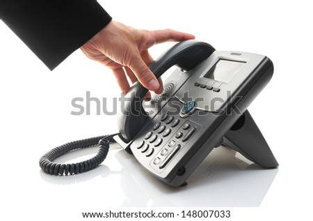 man's hand is picking up the phone - stock photo