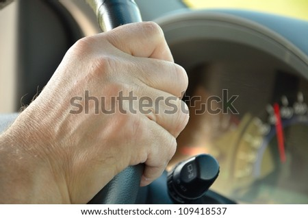 man's hand on the steering wheel of a car - stock photo