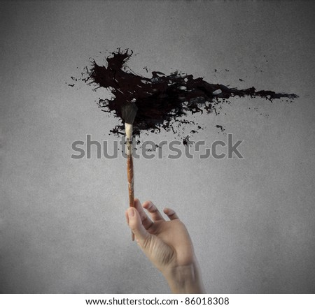 Man's hand painting in black with a brush - stock photo