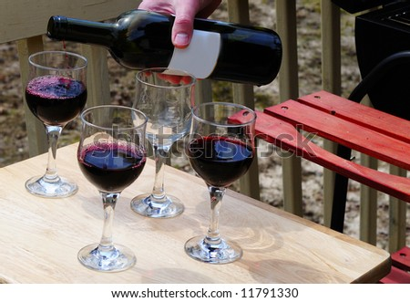 Man<s hand pouring wine into glasses in a BBQ party - stock photo