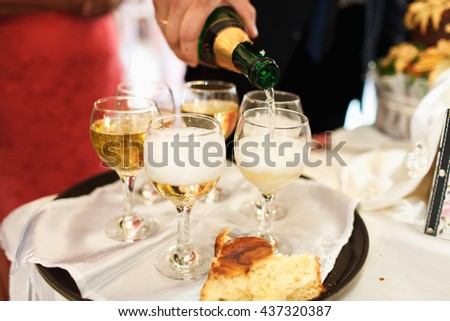 Man's hand pours a champagne into wineglasses on the tray - stock photo