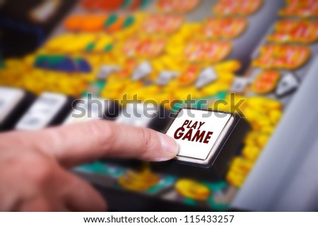 Man's hand pressing play button on a slot machine - stock photo