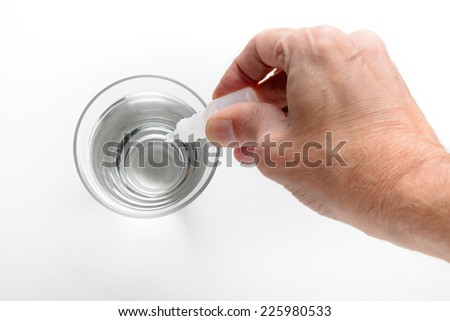 Man's hand putting drops of pharmacy in a glass of transparent water, on white background - stock photo
