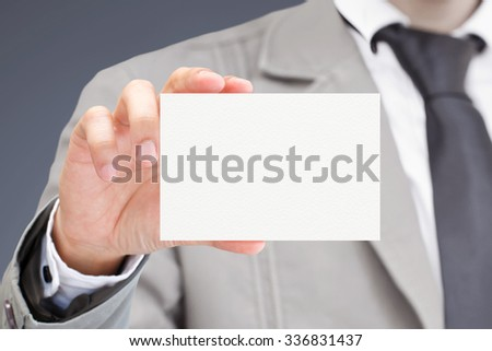 Man's hand showing business card. - stock photo
