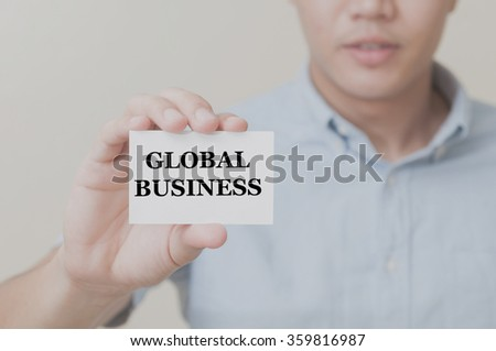 Man's hand showing GLOBAL BUSINESS  text on the card business card - closeup shot on white background - stock photo