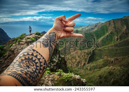 "Man's hand showing ""rock on"" sign against background of the beautiful mountain landscape - stock photo"
