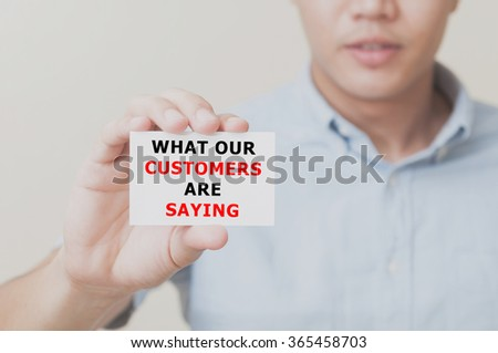 Man's hand showing WANT OUR CUSTOMERS ARE SAYING text on the card business card - closeup shot on white background. - stock photo
