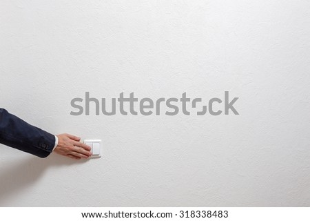 Man's hand turns off the light - stock photo