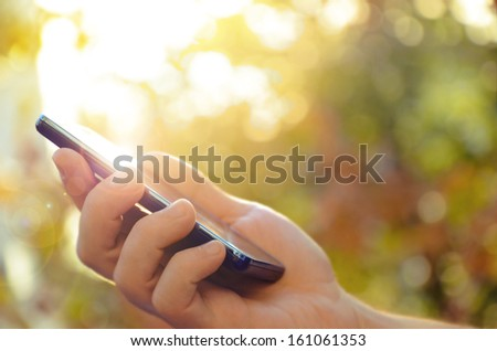 Man's hand using mobile smart phone - stock photo
