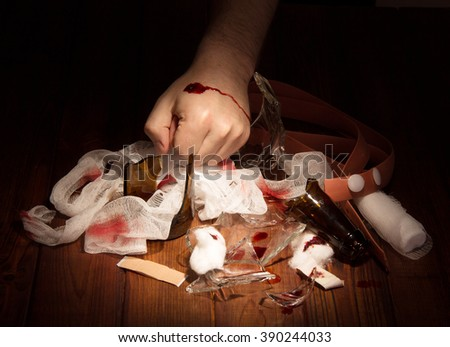 Man's hand with a bleeding wound and debris against the dark wood. - stock photo