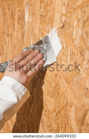 man's hand with a spatula puttied surface OSB - stock photo
