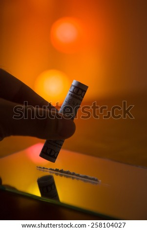 Man's hand with one hundred US dollars note to use cocaine . - stock photo