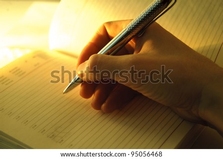 man's hand writing in a notebook - stock photo