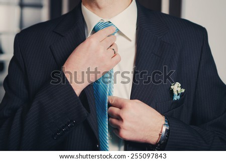 Man's hands closeup tying his blue tie knot - stock photo