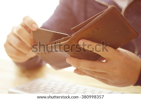 Man's hands holding a credit card in wallet and wireless computer keyboard , color filter image , business concept ,business idea - stock photo