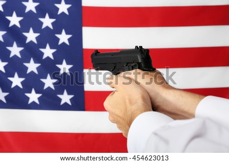 Man's hands holding gun on star and stripes background - stock photo